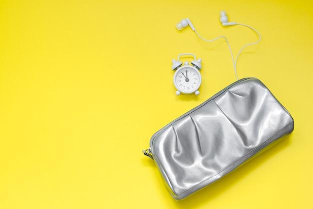 Concetto moderno di mattina della donna sveglia e cuffie d'argento della borsa cosmetica su fondo giallo
