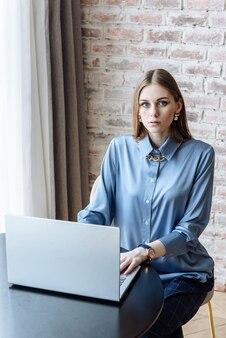 Impiegato moderno della donna che si siede al tavolo con il computer portatile