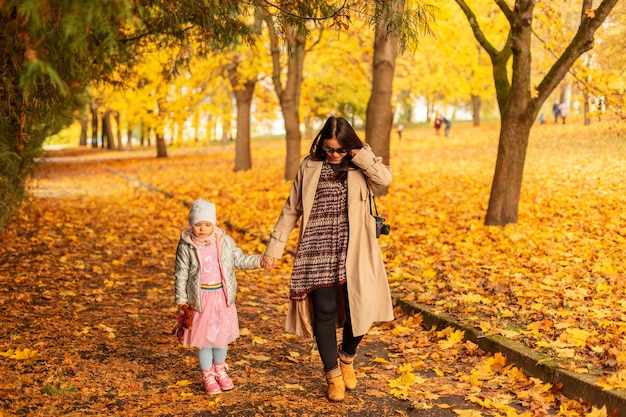 Mamma donna con figlia che cammina nel parco autunnale con fogliame giallo