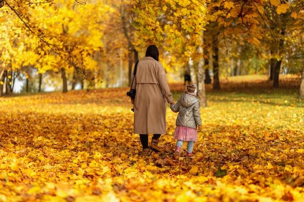 Donna mamma con figlia figlia in abiti alla moda che cammina sul fogliame autunnale giallo nel parco autunnale