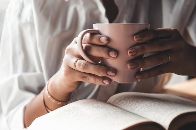 La donna al mattino beve caffè e legge il vecchio libro in una camicia bianca. istruzione, bevanda. manicure