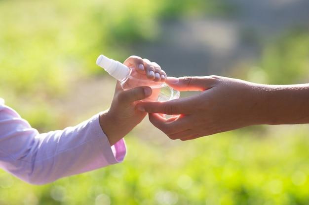 La donna madre dà al bambino un disinfettante, insegna a disinfettare le mani, foto ravvicinata