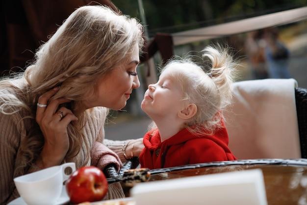 Donna madre bacio figlia a un tavolo in un caffè. felice coppia tradizionale, felicità familiare.