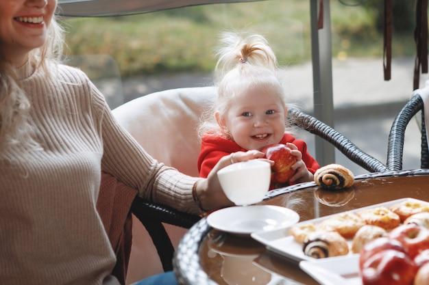Donna madre con figlia a un tavolo in un caffè. felice coppia tradizionale, felicità familiare.