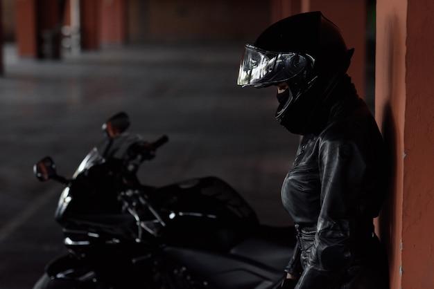 Donna motociclista alla guida della sua moto enduro o chopper vestito con eleganti abiti in pelle e dispositivi di protezione