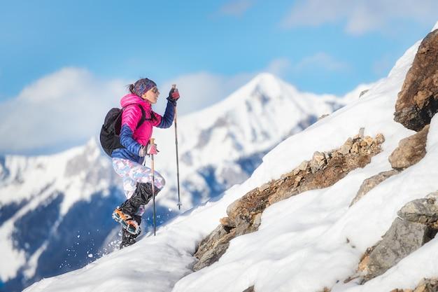 Alpinista donna durante una discesa con i ramponi su pendio innevato