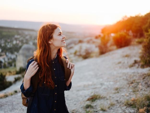 Donna in montagna all'aperto con uno zaino sulla schiena capelli rossi al tramonto