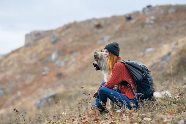 Donna in montagna all'aperto con il paesaggio di viaggio di amicizia del cane