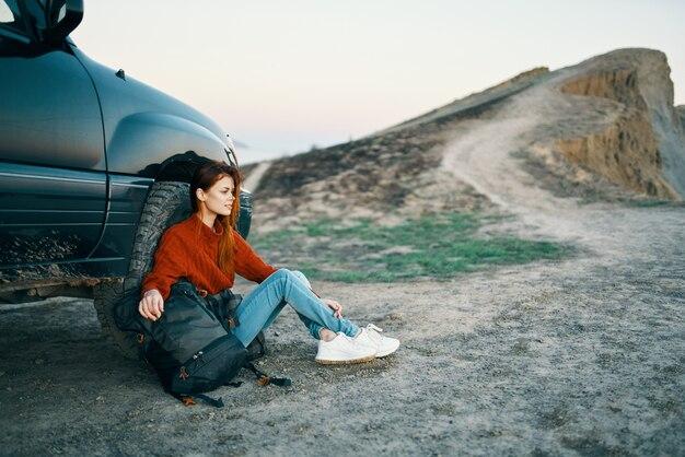 Donna in montagna sulla sabbia con uno zaino vicino alla vista dall'alto dell'auto