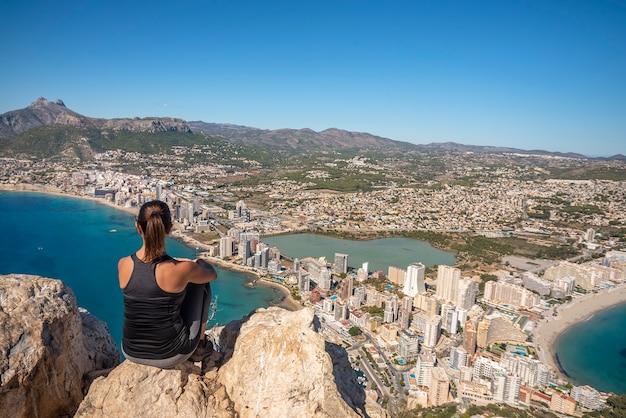 Donna in montagna seduta su una roccia a guardare la città