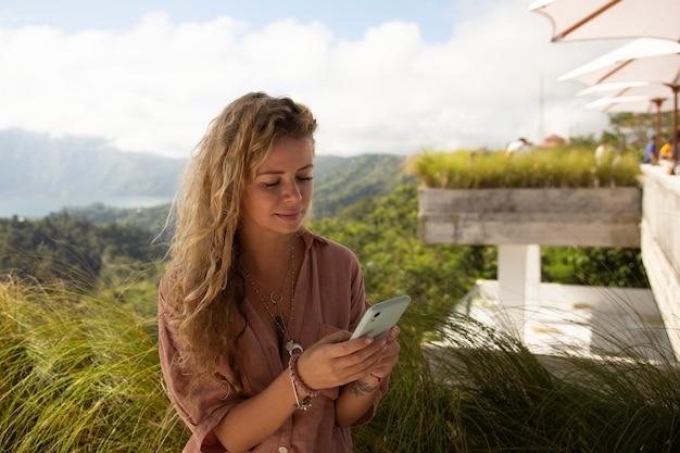Donna sulle montagne utilizza uno smartphone