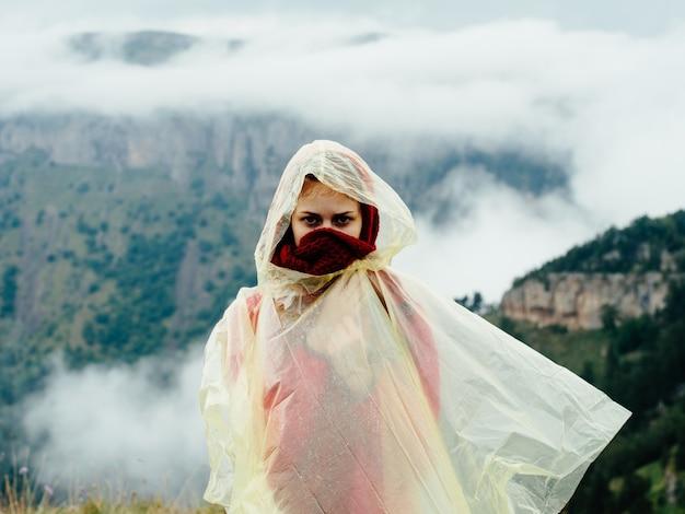 Donna in montagna con un mantello sulle spalle e montagne natura nebbia di aria fresca.