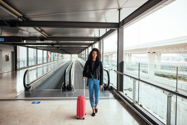 Donna nella passerella in movimento in aeroporto con una valigia rosa.