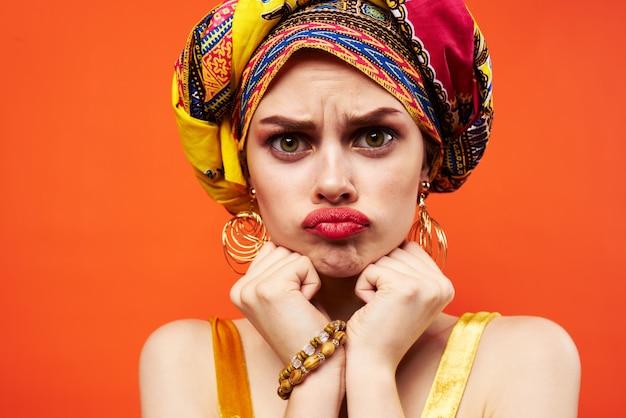 Donna in turbante multicolore con il trucco sul viso sfondo arancione