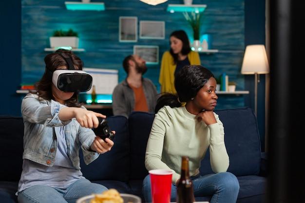 Donna e amici multietnici che giocano ai videogiochi online sperimentando la realtà virtuale con auricolare e controller wireless, divertendosi a tarda sera seduti sul divano.