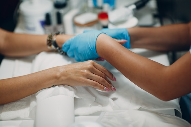 Donna nel salone dell'unghia che applica il manicure di bellezza. mani di donna di lusso.