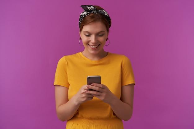 Donna trucco naturale che indossa abiti estivi alla moda alla moda e bandana con le braccia tenere il telefono emozione lettura guardando in basso sorridente faccia felice in posa sul muro viola