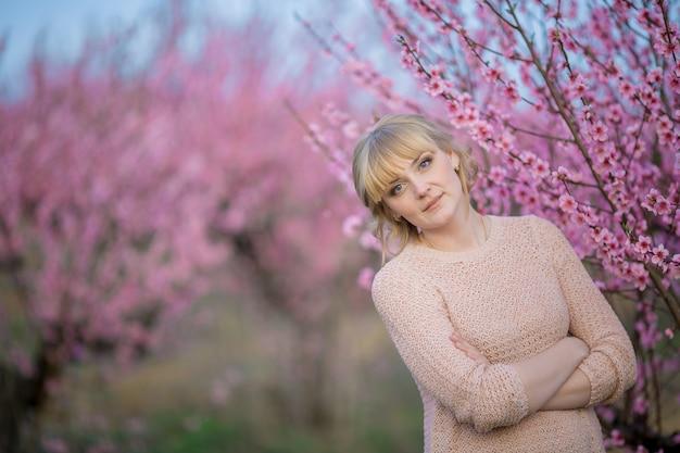 Donna sulla natura sullo sfondo di rami di un albero luminoso con fiori.