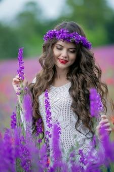 Donna sulla natura in un campo con fiori viola