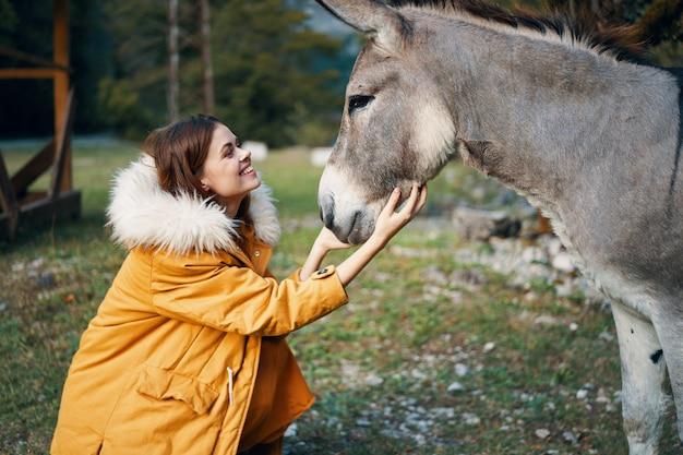 Donna in natura che accarezza un animale domestico di viaggio della campagna dell'asino