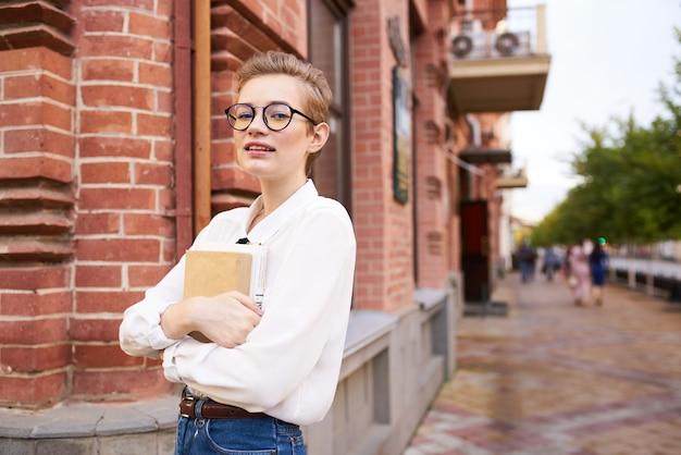 Donna vicino a un edificio in mattoni con gli occhiali con un libro in mano sull'istituto di istruzione di strada