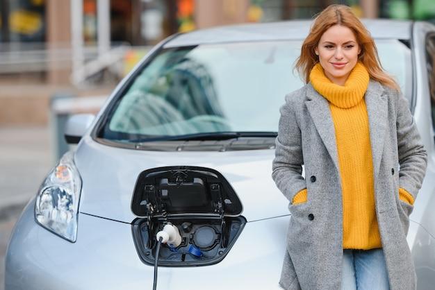 Donna vicino a un'auto elettrica a noleggio. veicolo caricato alla stazione di ricarica.