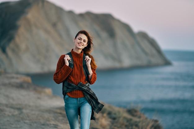 Donna vicino al mare in natura e montagne sullo sfondo modello di viaggio turistico
