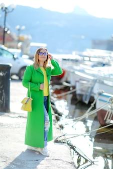 Una donna vicino al mare con i capelli biondi e gli occhiali da sole cammina all'inizio dell'autunno