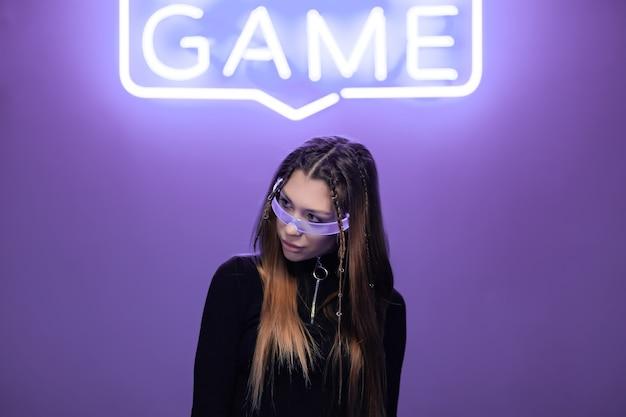 Donna con occhiali al neon in una stanza al neon con insegne al neon. foto di alta qualità
