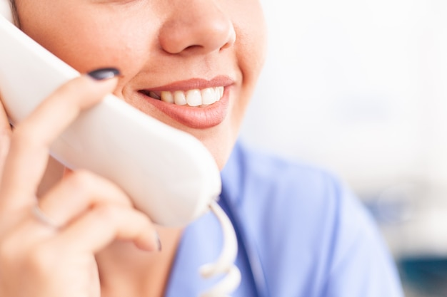 Infermiera donna che risponde al telefono nella reception dell'ospedale. infermiera, medico che ha una conversazione telefonica con una persona malata durante la consultazione, medicina.