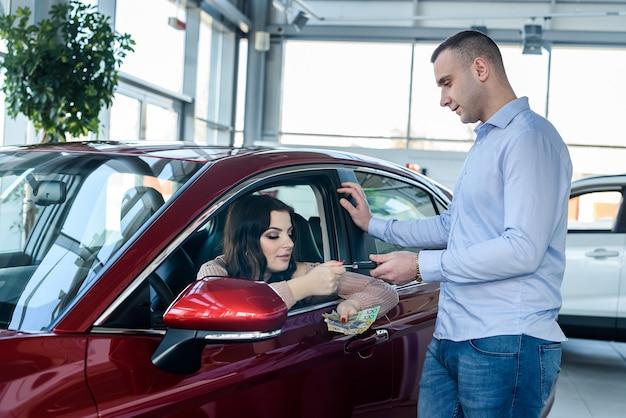 Donna che offre banconote in dollari australiani al rivenditore in showroom