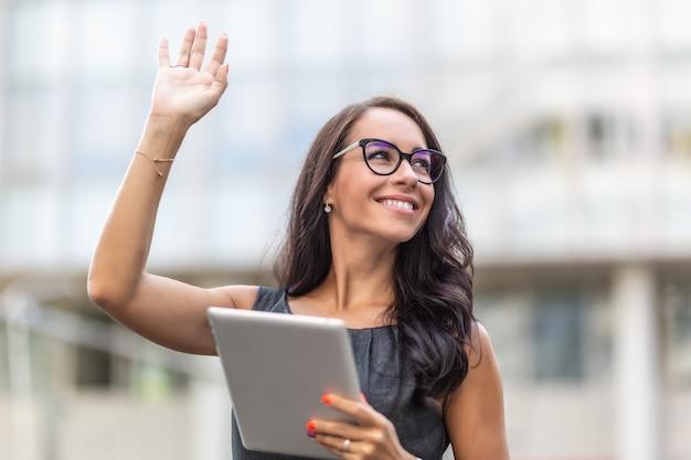 La donna in abiti da ufficio e occhiali sorride e saluta con in mano un tablet.