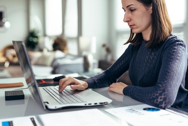 Donna in ufficio alla scrivania e lavora con il computer portatile.