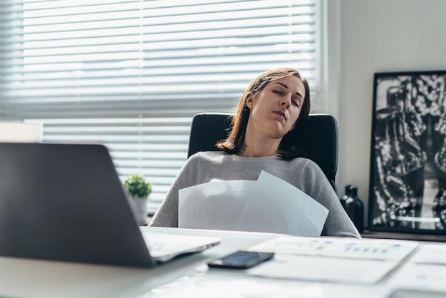 La donna in ufficio dorme seduta su una sedia con in mano dei documenti.