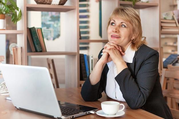 Una donna in ufficio sta lavorando su un laptop. lei sorride. una donna di mezza età, un adulto in un caffè.