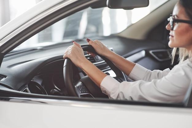 Donna in vestiti ufficiali che prova la sua nuova automobile nel salone dell'automobile