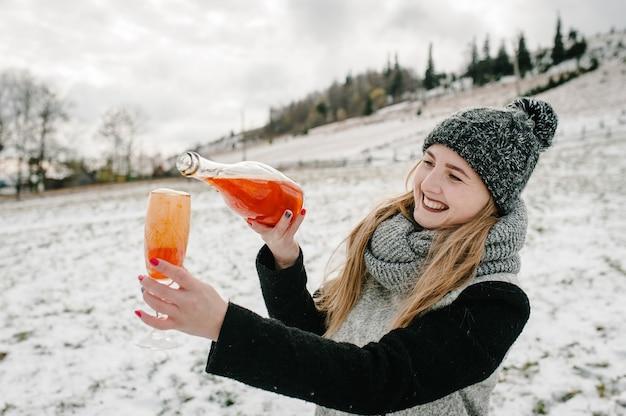La donna apre una bottiglia di champagne e si versa in un bicchiere sulle montagne invernali.