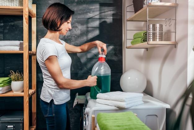 Donna apertura bottiglia di detergente liquido