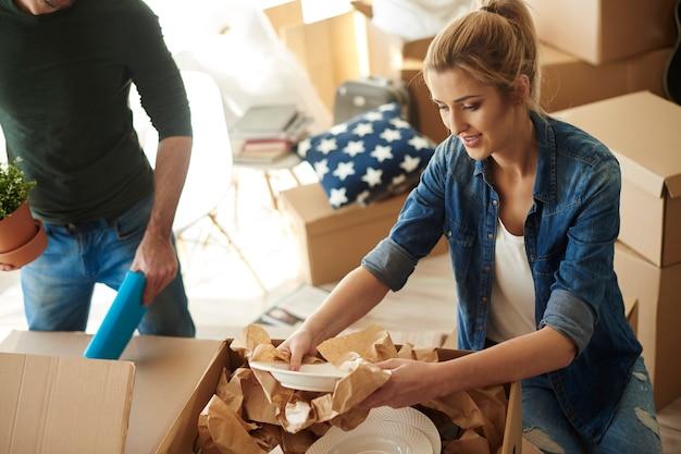 Donna che apre una scatola con cose di porcellana