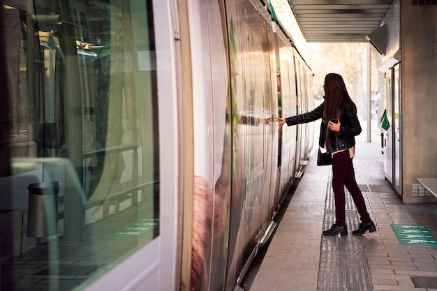 Donna che apre la porta per salire a bordo del tram