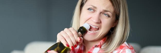 La donna apre la bottiglia di champagne con i suoi denti. concetto di alcolismo femminile