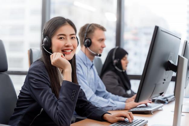 Operatore donna che indossa le cuffie lavorando sul computer e parlando con il cliente