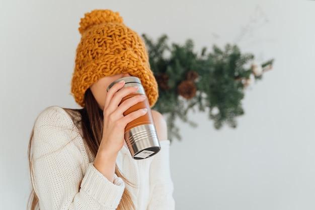 Donna con cappello arancione e tazza termo riutilizzabile in metallo il giorno di inverno di natale. vita sostenibile