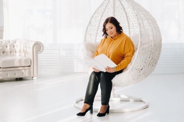 Una donna con una felpa arancione si siede su una sedia insolita con un libro in mano.
