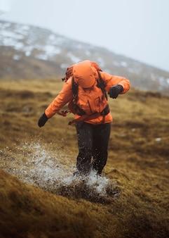 Donna in una giacca a vento arancione che fa un'escursione sotto la pioggia alle isole faerøer