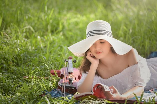 Donna all'aperto, bella ragazza romantica con i capelli scuri e vestito bianco che suona un violino nel parco di primavera. donna nel sole incandescente.