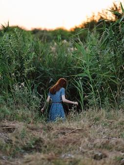 La donna all'aperto foglie verdi cammina l'estate