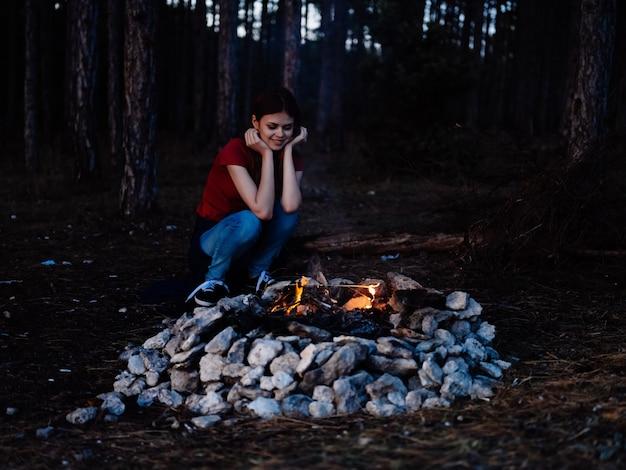 Donna all'aperto vicino al viaggio della foresta del turismo del fuoco di accampamento