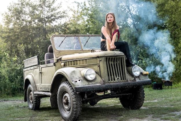 Donna all'aperto seduta sul cofano di un'auto militare