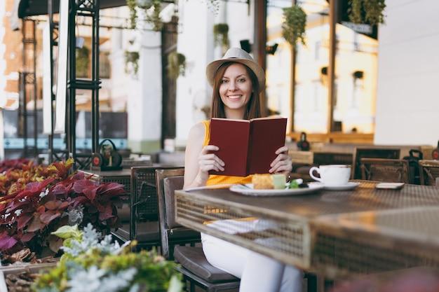 Donna in strada all'aperto caffetteria caffè seduto al tavolo in cappello, leggendo il libro con una tazza di cappuccino, torta, rilassante nel ristorante durante il tempo libero